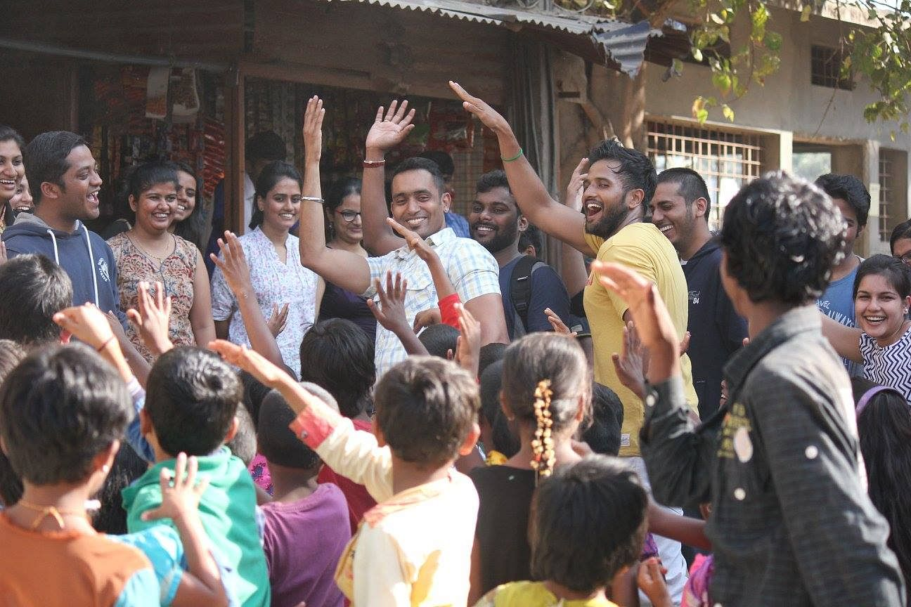 Volunteers dancing with children during the food drive