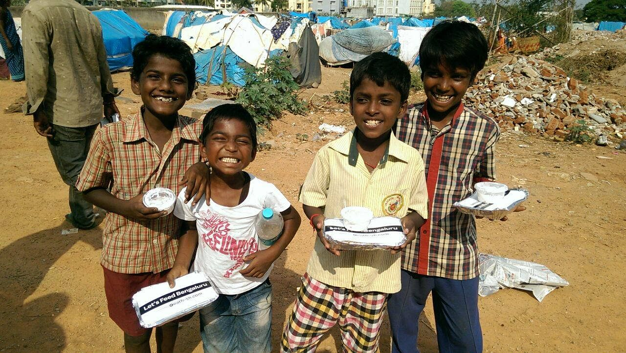 Happy children with food packets from Let's Feed Bengaluru