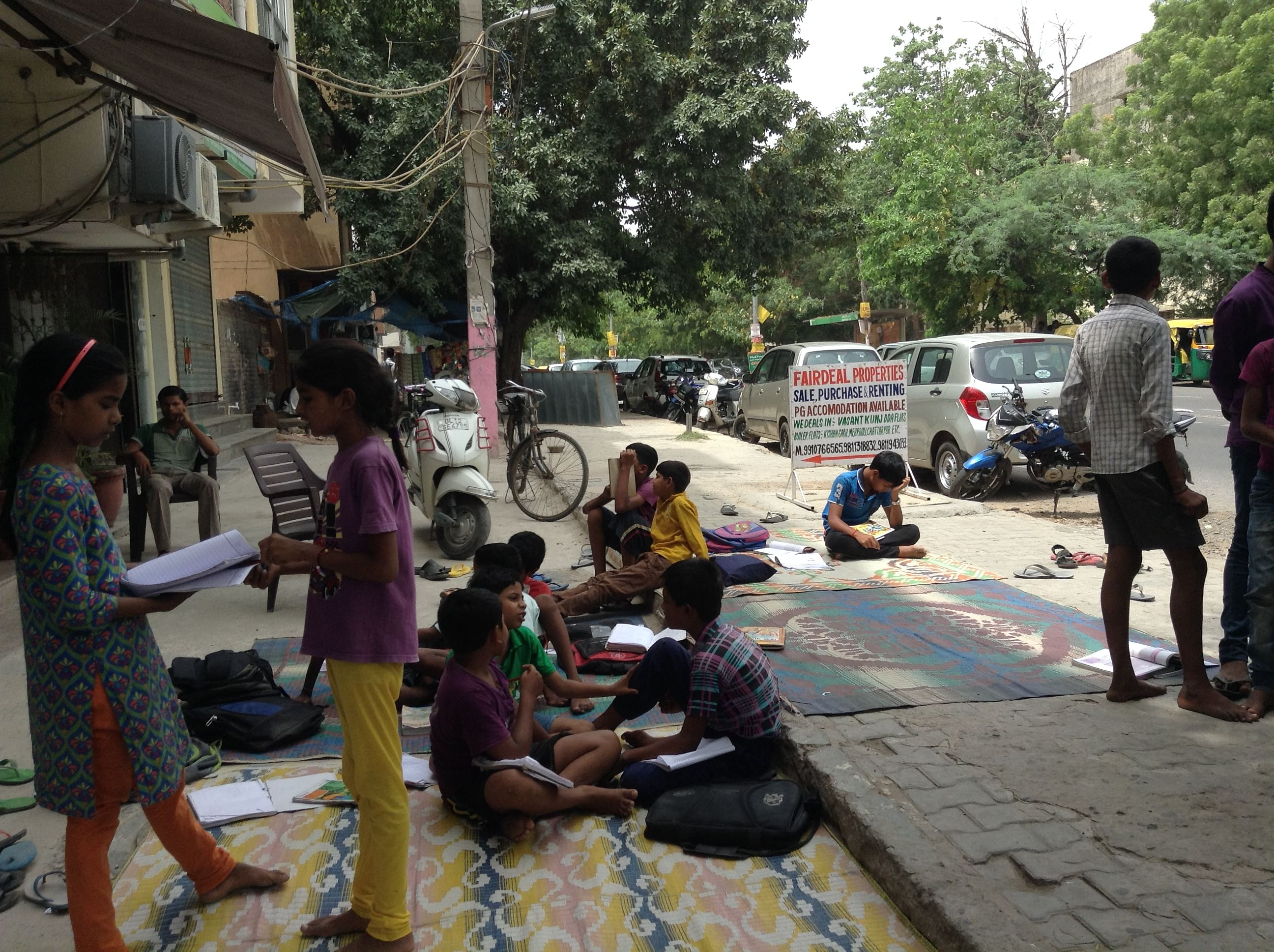 Children reading and learning on the pavement class-space