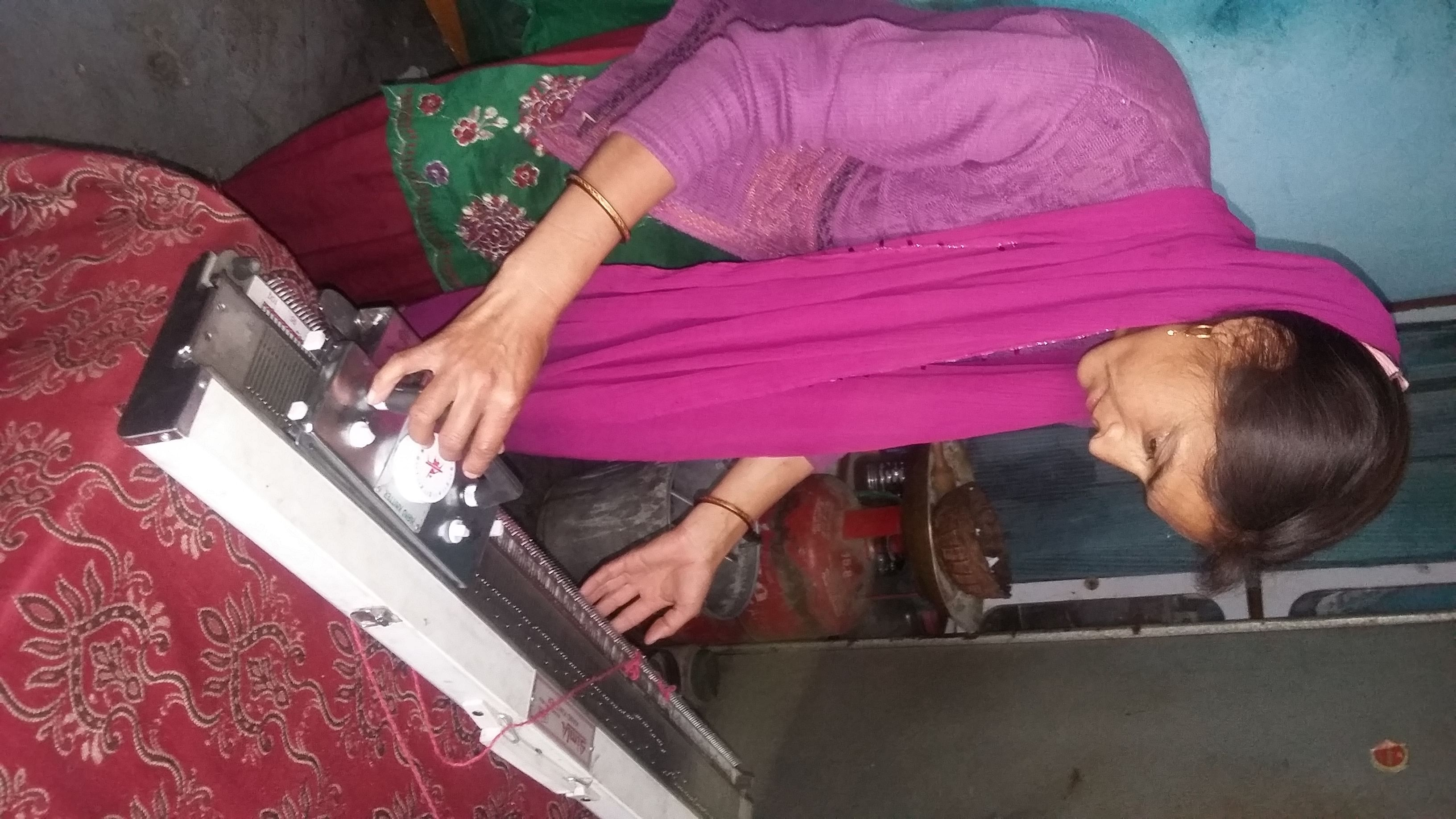 Gita Bisht, 33, of Chandrapuri, widowed in 2013, sees her knitting machine as the means to a better life someday. (Credit: Nitin Jugran Bahuguna\WFS)