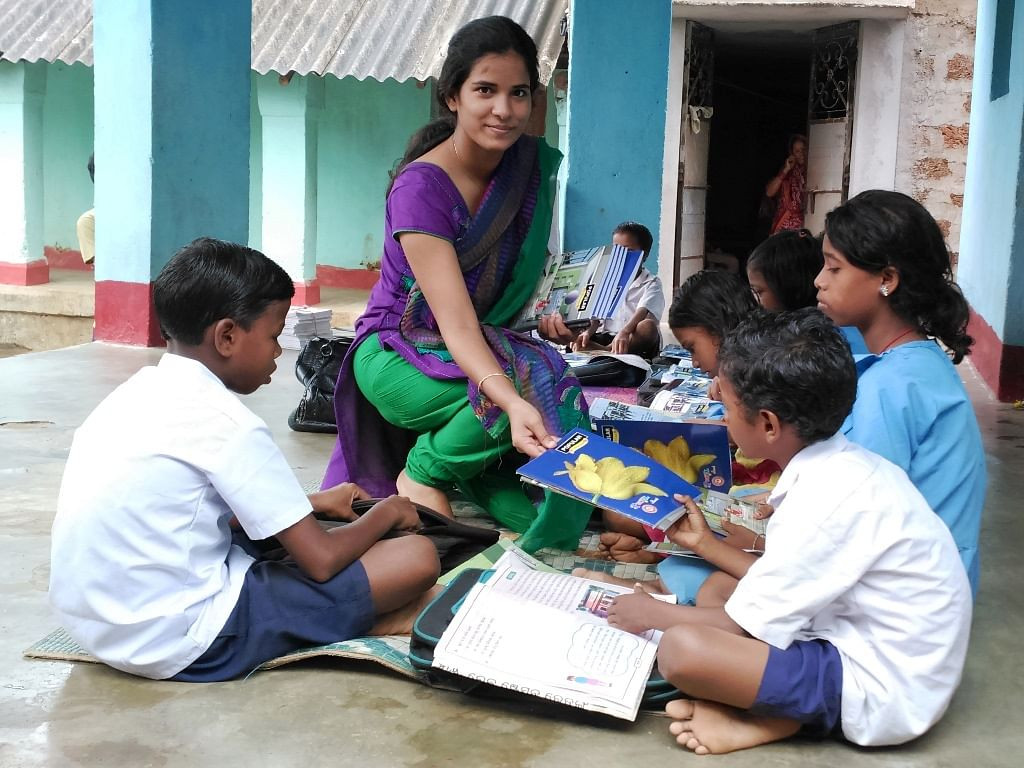 Maya distributing school supplies to underprivileged children