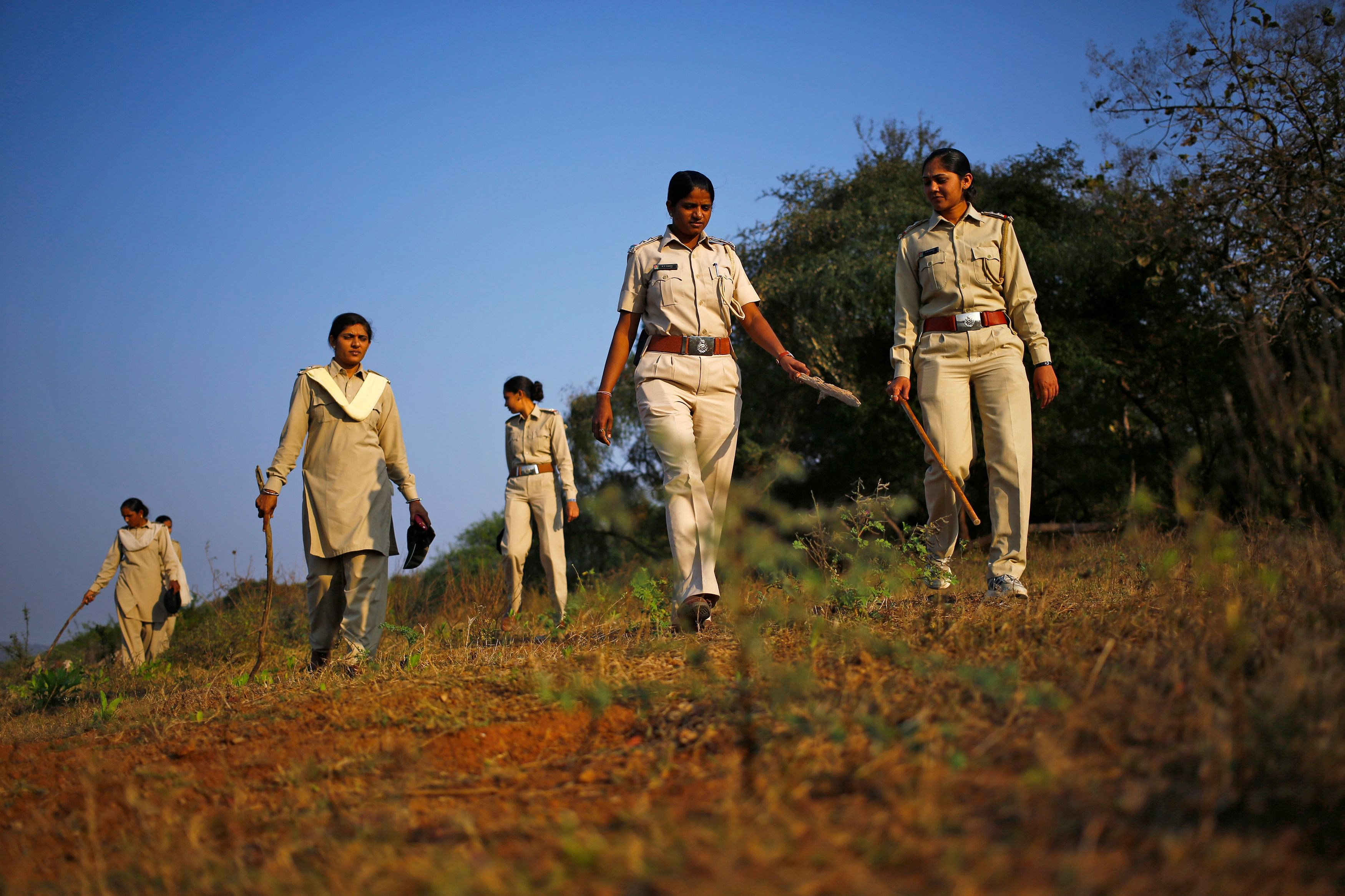 Forest guards carrying wooden sticks patrol the Gir National Park and Wildlife Sanctuary in Sasan, in the western Indian state of Gujarat December 1, 2014. The sanctuary, which is home to India's Asiatic lions, occupies an area of 1,412 square km and employed female guards, for the first time in the country, back in 2007. According to one of the female guards, they earn a monthly salary of around $148 for working almost 12 hours a day, six days a week. Picture taken December 1, 2014. REUTERS/Anindito Mukherjee (INDIA - Tags: ANIMALS ENVIRONMENT SOCIETY BUSINESS EMPLOYMENT) - RTR4H8SB