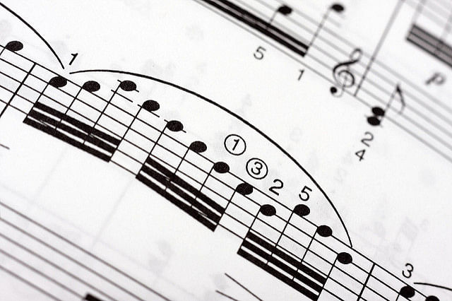 Groups of fast musical notes with a large legato arch over them on a music sheet, as part of a classical piece