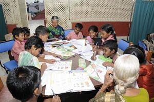 One of the senior residents of Anandam Old Age Home teach the children