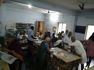 Senior citizens of Anandam Old Age Home distribute food packets during the Chennai floods.