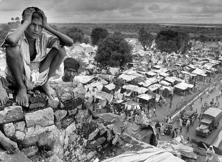 Boy sitting on rock ledge above refugee camp.