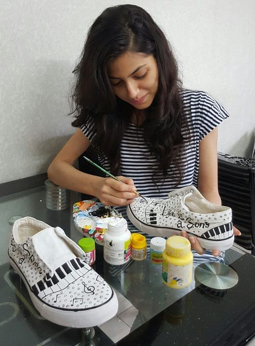 Nida Charfare hand-painting her designs