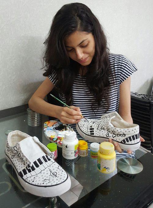 Nida Charfare hand-painting her designs