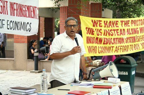 "A person wearing white shirt standing with a mic. In the background, there is college campus with some students sitting. A yellow banner with incomplete lines ""We Have.. Sue Us.. Indian Education.. Who Cannot"" Is visible. There is a loud speaker, water bottle and various books kept on a table."