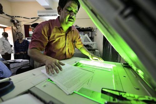 Image of a man photocopying a document on a white photocopying machine.