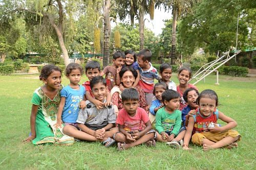 Meena with the children of nearby slums who come to her centre to study