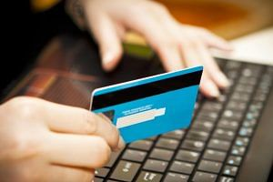 hand-holding-a-credit-card-at-a-computer-keyboard