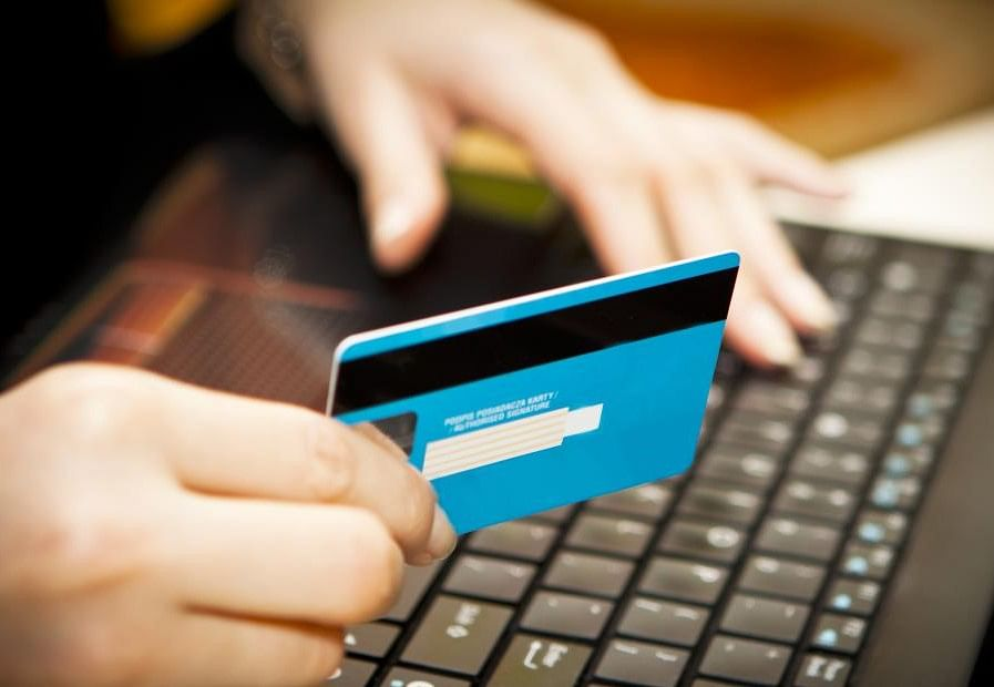 hand-holding-a-credit-card-at-a-computer-keyboard