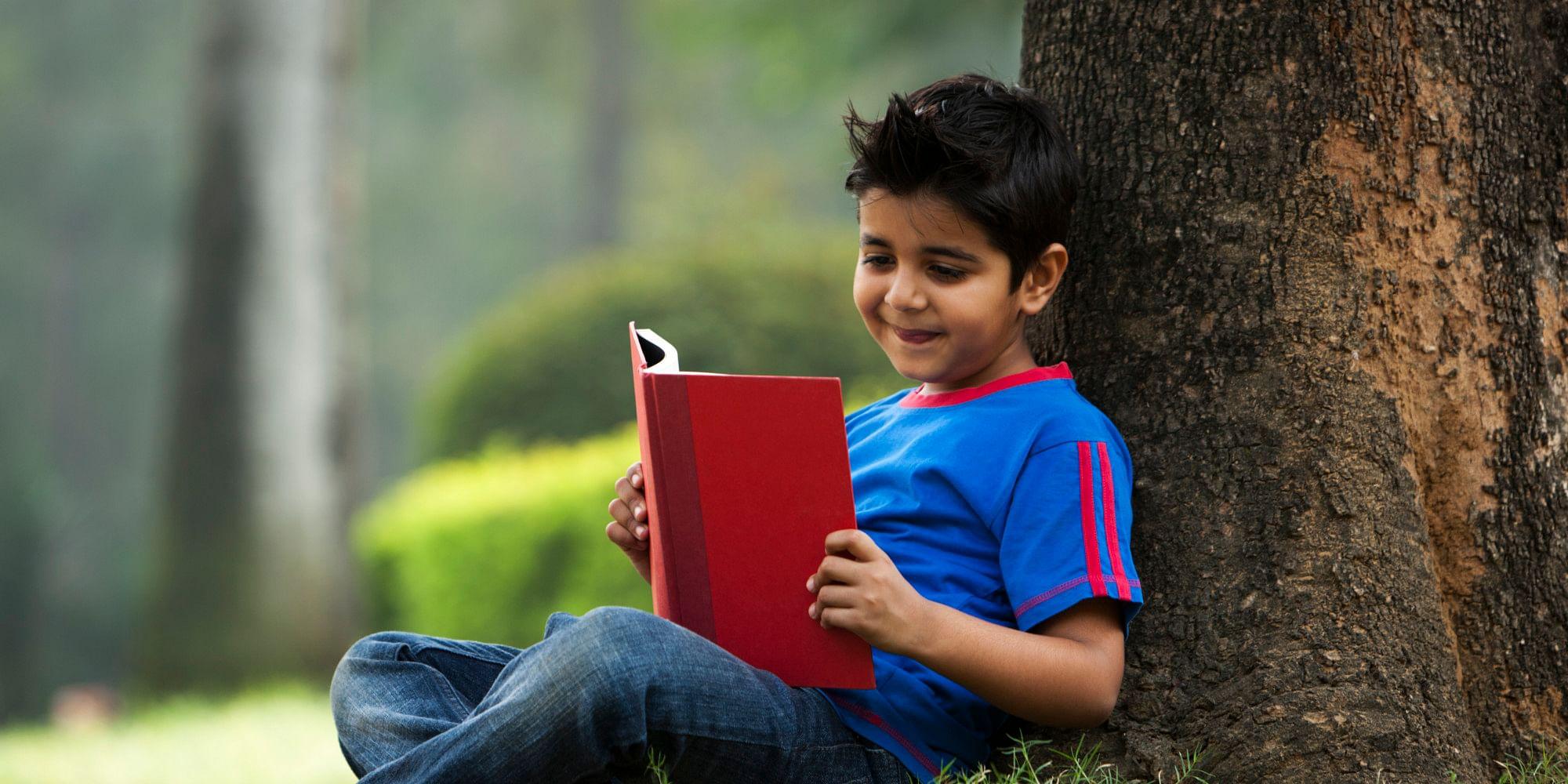 Boy (6-7) reading book under tree