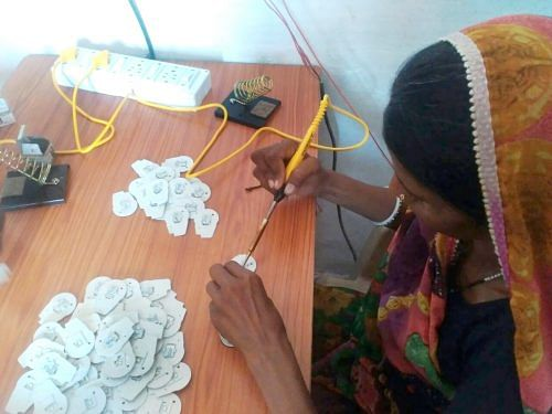 Tribal women like Rukmini are now familiar with all the parts of the portable solar lamp that they assemble efficiently. (Credit: Renu Rakesh\WFS)