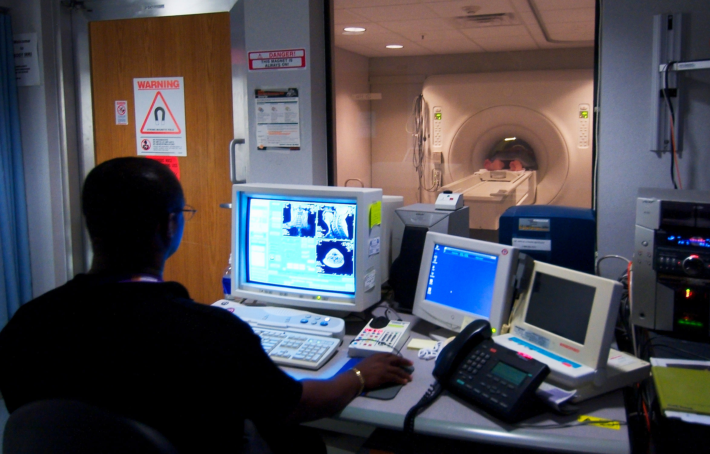 030819-N-9593R-228 National Naval Medical Center, Bethesda, Md., (Aug. 19, 2003) -- Civilian technician, Jose Araujo watches as a patient goes through a Magnetic Resonance Imaging, (MRI) machine at the National Naval Medical Center in Bethesda, Maryland. U.S.Navy photo by Chief Warrant Officer 4 Seth Rossman. (RELEASED)