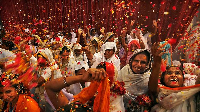 In this picture taken Sunday, March 24, 2013, Indian widows throw flowers during Holi celebrations, or the festival of colors, at an event organized by the NGO Sulabh at the Meera Sahbhagini Ashram in Vrindavan, India. The widows, many of whom at times have lived desperate lives in the streets of the temple town, celebrated Holi for the first time at the century old ashram. The women were banished by their families after their husband's deaths to the town where devotees believe Lord Krishna was born, for supposedly bringing bad luck. (AP Photo/Kevin Frayer)