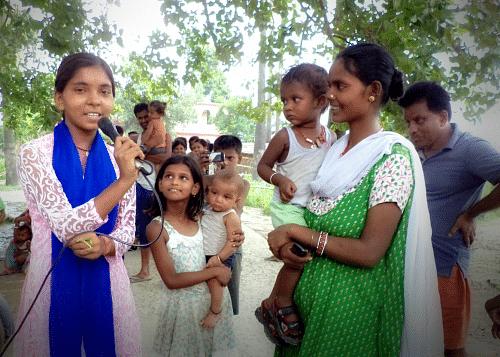 Nisha conducts a community meeting in a village in Bihar