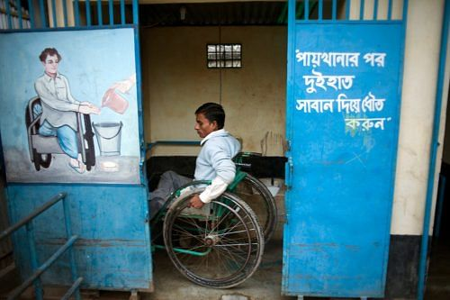 A disabled man uses the accessible latrine designed specifically to accommodate his needs. Photo Credit: WaterAid/Guilhem Alandry