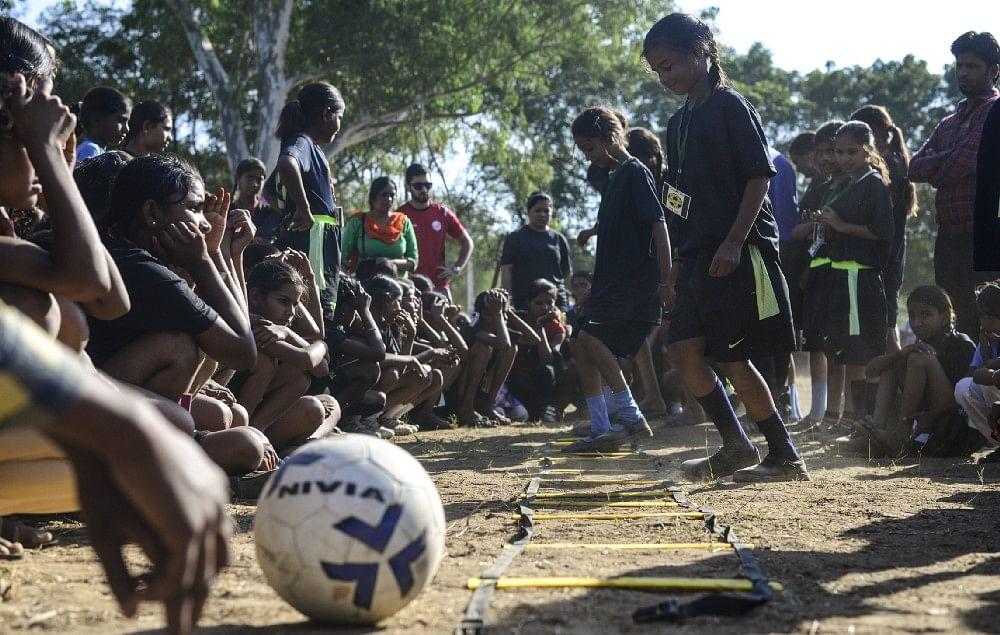 12—year—old Reeta gets training from coach during a football camp, in Meeno Ka Naya Gaon.