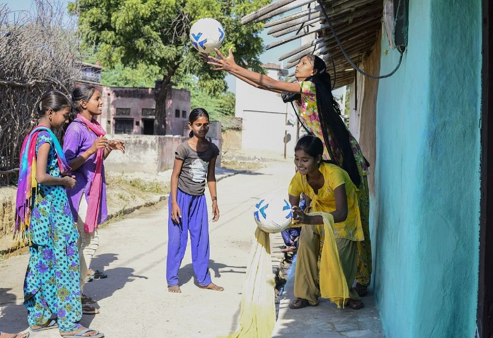 Anjali (yellow dress) along with other friends play during school lunch break, in Meeno Ka Naya Gaon.