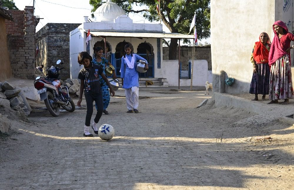 12 year old Monica patting the ball while Nisha and Sonia go to fetch water from a nearby well, in Sakariya village.