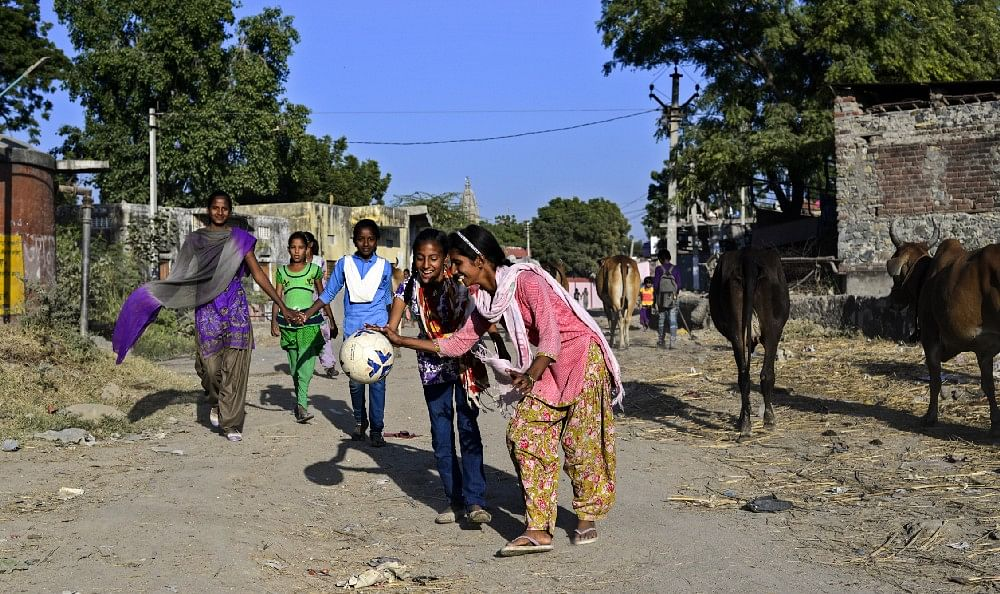 Students of 9th class; Sunita and Pooja play around on the way to ground, in Sakariya.