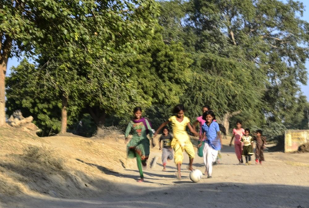 12 — year — old and Students of 6th class, Monica and Pratibha along with others chasing the ball on the way to ground, in Sakariya.