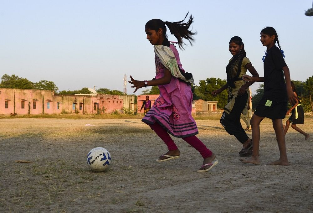 15—year—old Pooja chase the ball during a evening practice, in Sakariya.