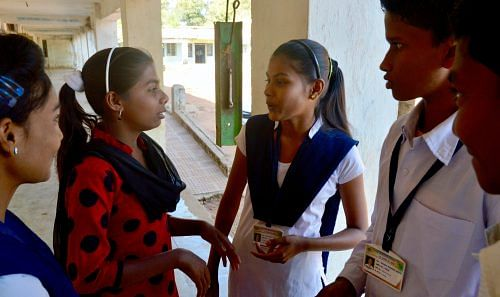 Payal Mishra (in red kurta) talks to Vaishnavi Sakhre (3rd from left) and Chandan Wasey (4th from left) at Zilla Parishad High School in Saoli block's Patri village. (Credit: Dilnaz Boga\WFS)