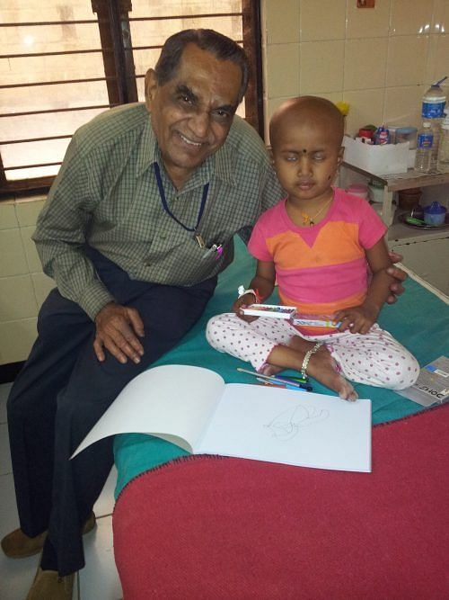 Ramaswamy happily helps child in some drawing activity in a hospital ward
