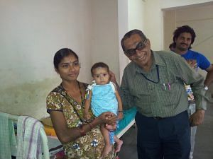 Ramaswamy with a mother and child in a hospital