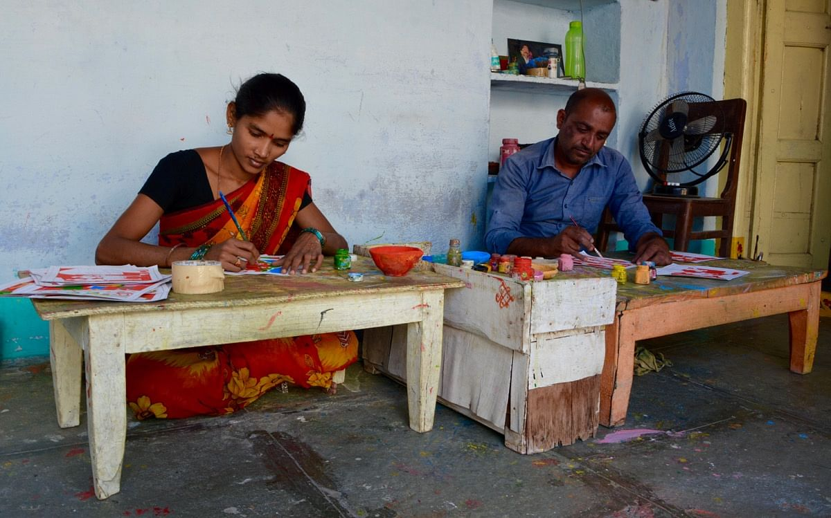 Artists at work creating Cheriyal Paintings
