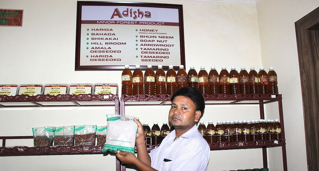 At a Bhubaneswar government outlet for minor forest products, a shop assistant holds up their fastest moving item, the powdered millet packet, whose sale has doubled in the last year. (Photo by Manipadma Jena)