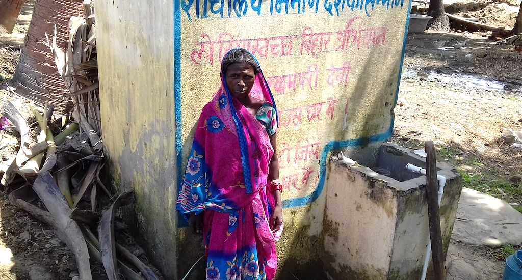A village woman is standing in front of a newly constructed toilet at her home. (Photo by Mohd Imran Khan)