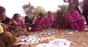 Women of self-help group in Ghagra village of Gumla district in Jharkhand distributing kitchen garden seeds among themselves. (Photo by Soumi Kundu)