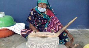 A woman uses jata, a traditional grinding stone, to make sattu. (Photo by Mohd Imran Khan)