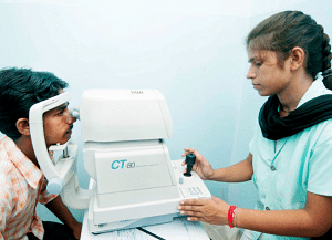 Patient taking an eye exam with an optometrist at AJEH. (Source: Milaap)