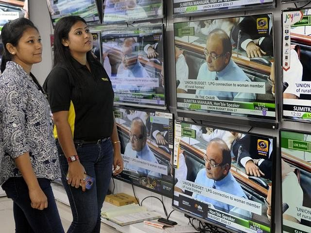 People watch Union Budget presentation by finance minister Arun Jaitely on TV sets at a showroom last year.