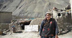 Tashi Tsonma of Rumbak Village fetches hot water from a solar heater. (Photo by Sharada Balasubramanian)