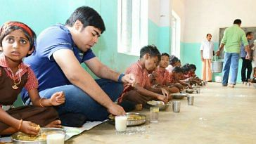 Wayanad District Collector Suhas sharing a meal with children at one of the tribal schools. For representational purposes only. Courtesy: Wayanad District Administration.