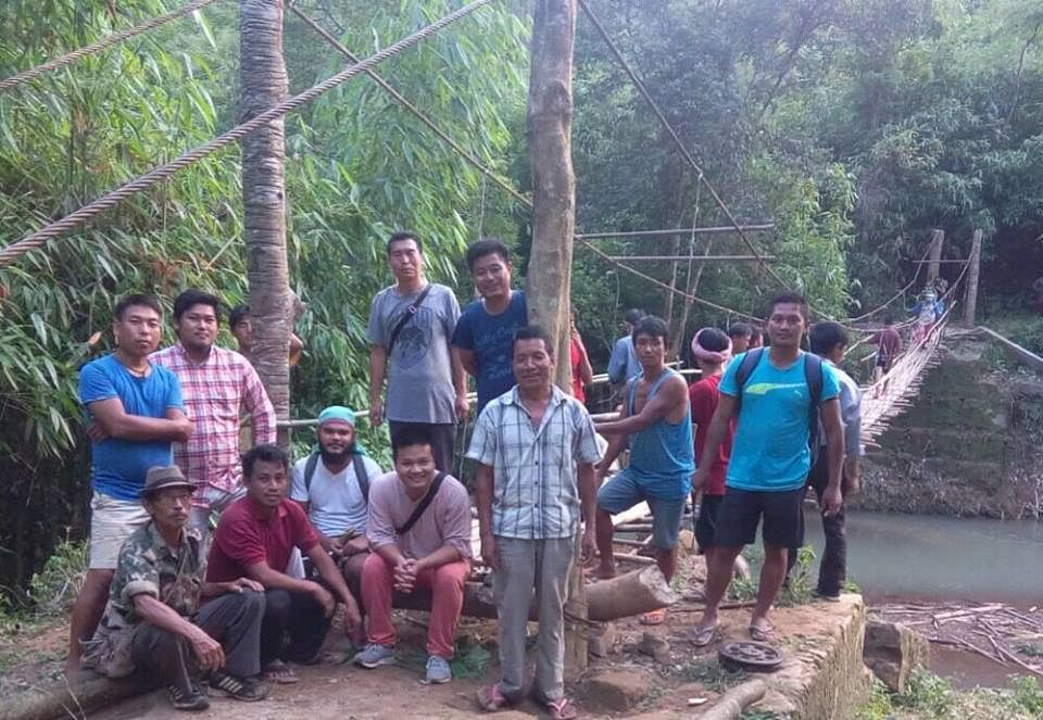 Aching Zeme standing in a shirt and grey pant with other villagers who worked on the hanging bridge. (Source: Facebook/Aching Zeme)