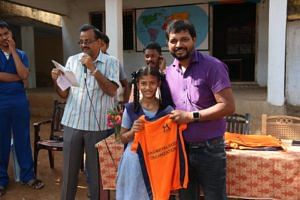 Sridhar Reddy distributing sports T-shits to the Gandhi Park School in his hometown.