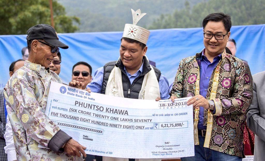 A local resident receiving a cheque from Chief Minister Pema Khandu and MoS (Home) Kiren Rijiju. (Source: Twitter/Kiren Rijiju)
