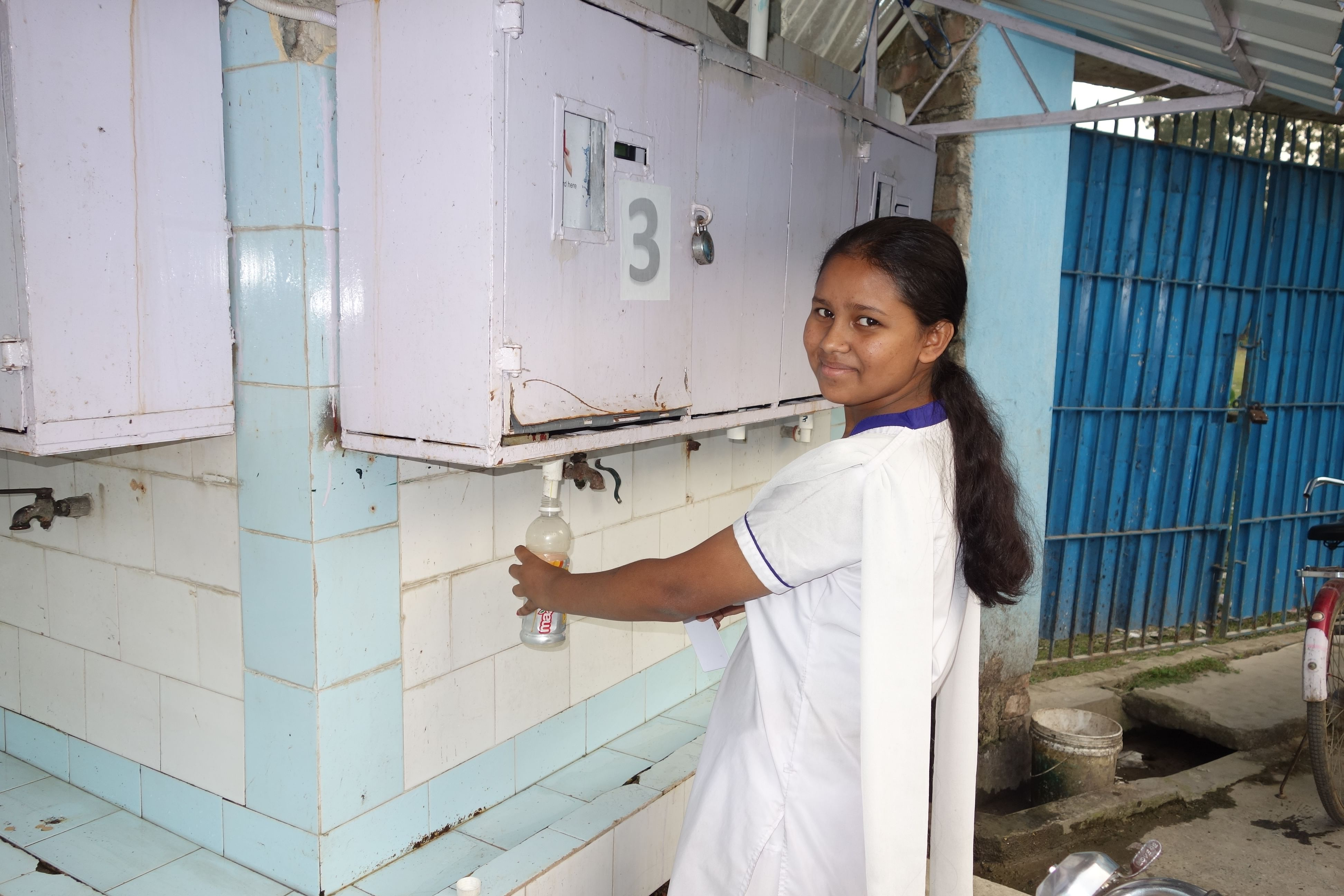 Students from Dhapdhapi High School taking arsenic free water using her electronic card.