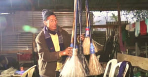 Usham Krishna Singh standing with his brooms made of plastic bottles. (Source: YouTube)