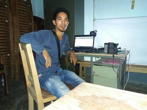 Dilseng Sangma with his laptop on which he watched YouTube videos on how to make these biodegradable plates.