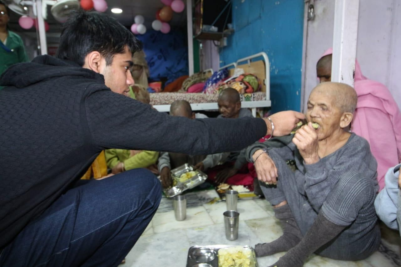 Vivhan feeding an elderly citizen.