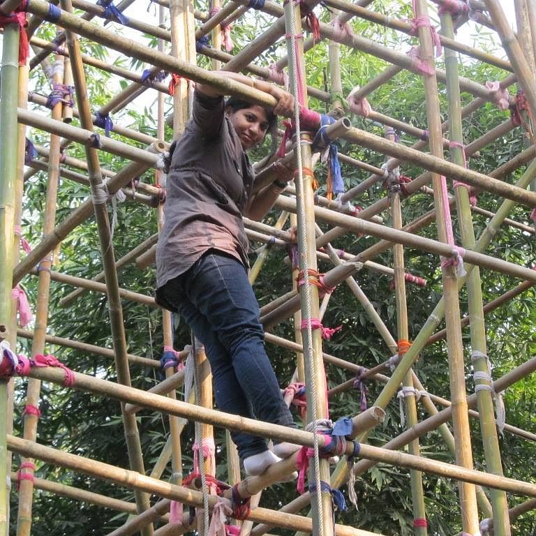 Purnima Barman climbing up a bamboo structure to observe the Greater Adjutant Stork. (Source: Facebook)