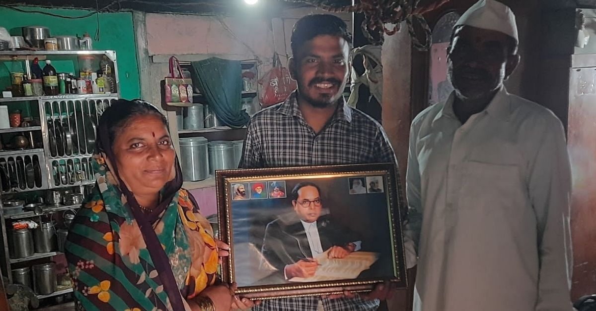 raju kendre stands with his parents with a photo of BR Ambedkar